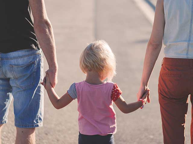 Photo of a man, woman and child walking away from the camera